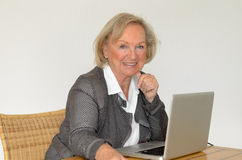 Senior woman in business look in front of a silver laptop Stock Photos