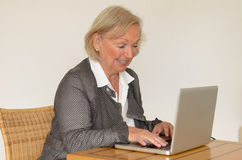 Senior woman in business look in front of a silver laptop Stock Photo