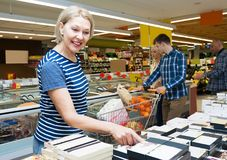 Senior woman buying candies in a supermarket Stock Photo