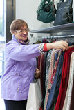Senior woman buying clothes in   store. Royalty Free Stock Photo