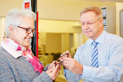 Senior woman buying glasses at Stock Photos