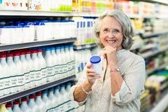 Senior woman buying milk Stock Photo