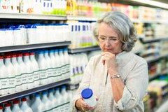 Senior woman buying milk Royalty Free Stock Image