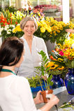 Senior woman buying plant paying flower market Royalty Free Stock Image