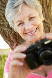 Senior woman with camera smiling Royalty Free Stock Photos