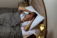 Senior woman cannot sleep at nighttime while holding her head wi Royalty Free Stock Photo