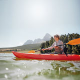 Senior woman canoeing on a summer day Royalty Free Stock Photography