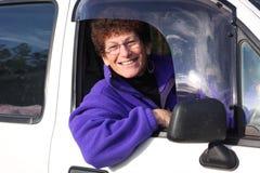 Senior woman in car. Senior woman smiling sitting in her car Royalty Free Stock Photo