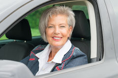 Senior woman in car. Happy and smiling senior woman in black car Stock Photo