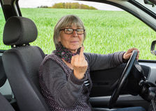 Senior Woman in the car shows middle finger Royalty Free Stock Photos