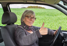 Senior Woman in the car with thumbs up.  royalty free stock photos