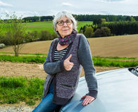 Senior Woman with car and thumbs up Stock Photos