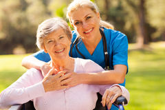 Senior woman caregiver. Happy senior women in wheelchair outdoors with caring caregiver