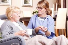 Senior woman and caregiver at home royalty free stock photos