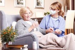 Senior woman and caregiver at home Royalty Free Stock Image