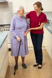 Senior woman and carer in kitchen. Senior women and carer in kitchen being helped to walk stock image