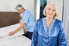 Senior Woman With Caretaker Making Bed At Nursing Stock Images