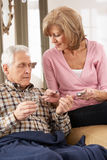 Senior Woman Caring For Sick Husband Stock Photography