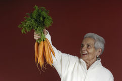 Senior woman with carrots Stock Images