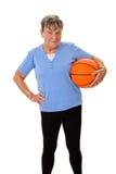 Senior woman carrying a basketball Royalty Free Stock Photos