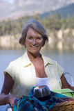 Senior woman carrying picnic hamper beside lake, smiling, portrait Royalty Free Stock Images