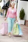 Senior Woman Carrying Shopping Bags Stock Photos
