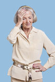 Senior woman in casuals suffering from headache against blue background Stock Photography
