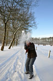 Senior woman catching a snowball in snowy field Royalty Free Stock Photography