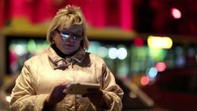 Senior woman with cell phone standing near the road in nighttime stock footage