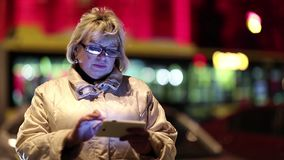 Senior woman with cell phone stands near the road in nighttime stock footage