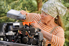 Senior woman changing engine oil Royalty Free Stock Image