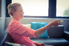 Senior woman changing tv channel Royalty Free Stock Photography