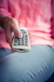 Senior woman changing tv channel Stock Image