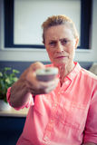 Senior woman changing tv channel Royalty Free Stock Photo