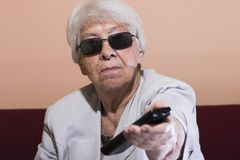 Senior woman changing the TV channel. With a remote control Stock Image
