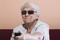 Senior woman changing the TV channel Royalty Free Stock Photography