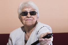 Senior woman changing the TV channel Royalty Free Stock Photo