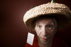 Senior woman in a cheap straw hat royalty free stock photography