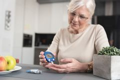 Senior woman checking blood sugar level at home. Senior woman with glucometer checking blood sugar level at home. Diabetes, health care concept royalty free stock photo