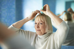 Senior woman checking hairline for hair loss. Old caucasian woman applying lotion to prevent hair loss, looking at mirror in bathroom stock images