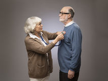 Senior woman checking heart beat. Old couple. Senior women taking care, checking heart beat of husband with stethoscope stock photography