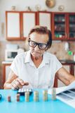 Senior woman checking her finances and investments. Senior woman at home checking her finances and investments royalty free stock photo