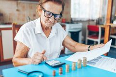Senior woman checking her finances and investments. Senior woman at home checking her finances and investments royalty free stock photos