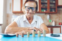 Senior woman checking her finances and investments. Senior woman at home checking her finances and investments stock photography