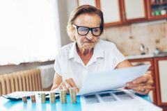Senior woman checking her finances and investments. Senior woman at home checking her finances and investments royalty free stock photography