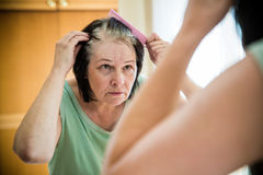 Senior woman checking her gray hair roots Royalty Free Stock Image