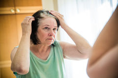 Senior woman checking her gray hair roots Royalty Free Stock Images