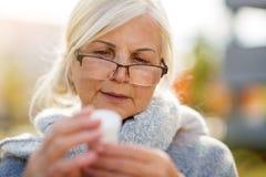 Senior woman checking label on medication stock photo