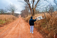 Senior Woman Checking for Mail at a Rural Mail Box. Along a lonely country road on an autumn day a woman checks for her mail Royalty Free Stock Photography