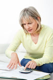 Senior woman checking pension. Approval certificate with calculator at home Royalty Free Stock Photo